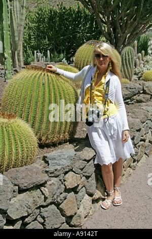 Blonde Girl Standing by a Golden Barrel Cactus, Palmitos Park, Gran Canaria. Botanical Gardens - Stock Image