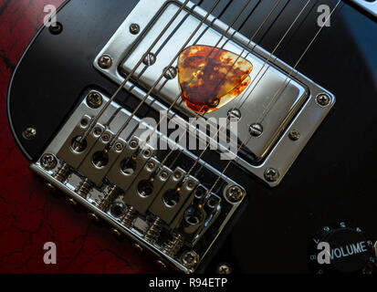 Tortoiseshell guitar pick or plectrum resting on the strings of an electric guitar. - Stock Image