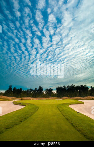 Portrait shot of golf course showing a narrow entrance to a Green with an amazing sky. - Stock Image
