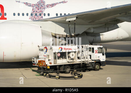 A Total aviation fuel truck refuelling an Austrian Airlines passenger airliner at Vienna Airport - Stock Image