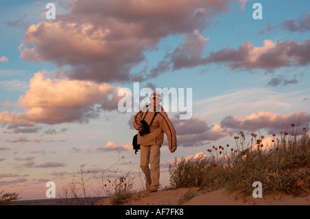 walking man photographer Nick Chaldakov clouds Primorsko Bulgaria - Stock Image