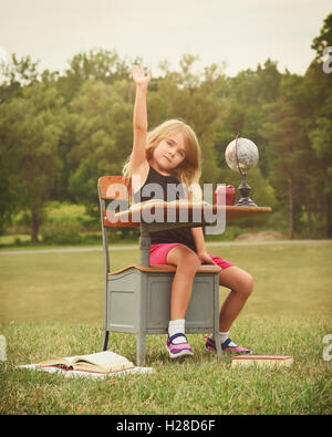 A little child is sitting at a school desk outside raising her hand with books for a question, idea, back to school - Stock Image