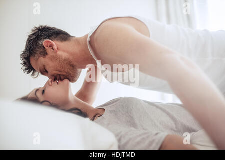 Intimate young couple lying together on bed and kissing. Romantic young couple on bed enjoying foreplay. - Stock Image