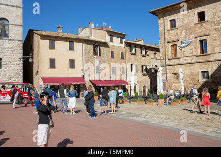 Tourists and visitors stand in Piazza Grande, main square of Montepulciano, historic hilltop town in Tuscany,Italy - Stock Image