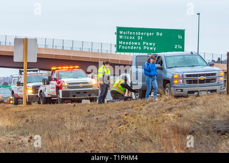 Woman motorist receiving assistance for flat tire along Interstate 25 in evening, Castle Rock Colorado US. Photo taken in March. - Stock Image
