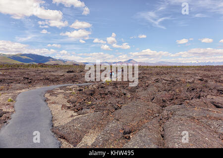 Tourists are hiking on an asphalt path on top of the lave flows of Craters of the Moon National Monument & Preserve - Stock Image