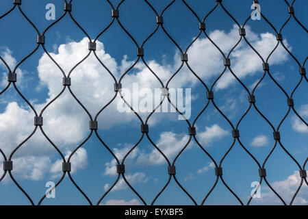 clouds and blue sky behind mesh fence - Stock Image
