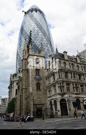 The Gherkin building peaking from behind an old historic building and church - Stock Image