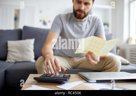 Contemporary young man holding payment bill while pressing calculator buttons and counting monthly budget - Stock Image