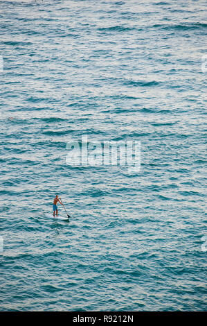 Distant view of a single man paddle boarding in sea - Stock Image