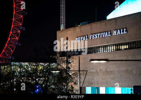 A view of the Royal Festival Hall next to the London Eye at night - Stock Image
