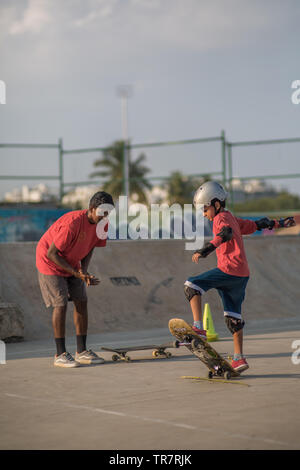 A child being coached while skateboarding in a skatepark in Bangalore, India. - Stock Image