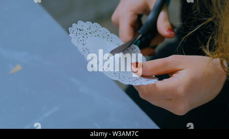 Professional woman decorator, designer cutting paper pattern - Stock Image