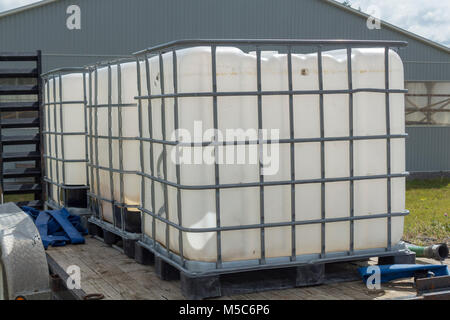 Three water containers on a flat bed trailer on a farm for watering livestock - Stock Image