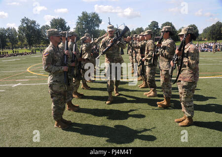 A platoon leader twirls his weapon while marching through opposing ranks of Soldiers who completed weapon tosses to each other as he passed through during the 23rd Quartermaster Brigade Drill and Ceremony Competition Aug. 23 at Fort Lee. - Stock Image