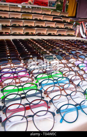 Large selection of eye wear glasses and sunglasses displayed for sale on a market stall. - Stock Image