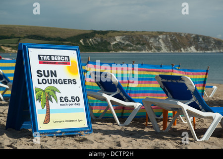 Sun loungers for hire and rent  for £6.50 per day on Swanage beach in Dorset - Stock Image