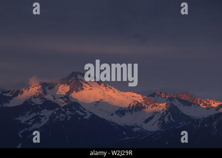Last sunlight of the day touching the peak of Mount Hoch Ducan, Canton of Grisons, Switzerland. - Stock Image