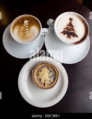 A cappuccino,a flat white coffee and a mince pie on white crockery. Taken from above. Triangular arrangement, three - Stock Image