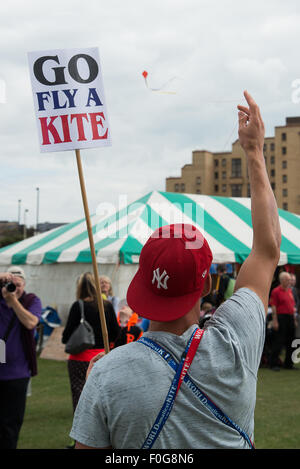 Portsmouth, UK. 15th August 2015. A kite seller demonstrates the worlds smallest kite as his photograph is taken - Stock Image