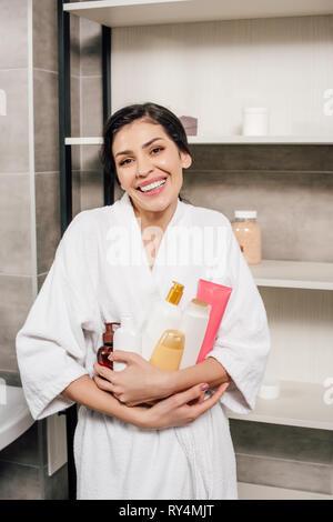 woman in white bathrobe holding bottles in bathroom - Stock Image