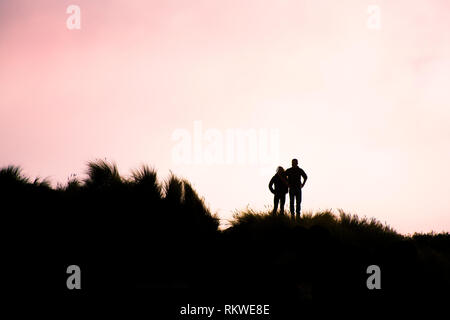 People silhouetted against the evening light as they stand amongst the marram grass on the dunes at Crantock Beach in Newquay in Cornwall. - Stock Image