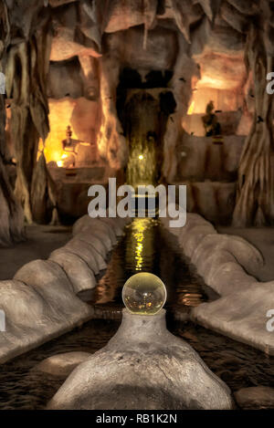 Thailand cave interior with illuminated statues and figures of hermits living in caves. Ruesi Forest, Pattaya, Thailand, Southeast Asia - Stock Image