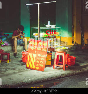 A quiet night in Hoi An as a streetfood vendor plays on his mobile phone - Stock Image