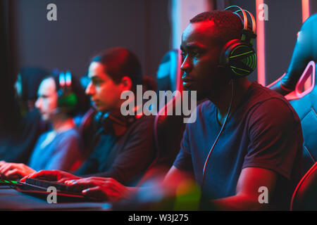Serious busy interracial men focused on video game development sitting in line and using modern computers - Stock Image