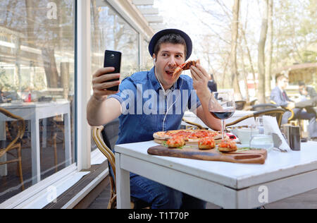 Handsome hunger man eating pizza and showing off in a video conference with his friends. Traveler abroad and free roaming concept. - Stock Image