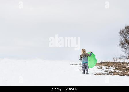Rear view of child carrying toboggan in snow - Stock Image