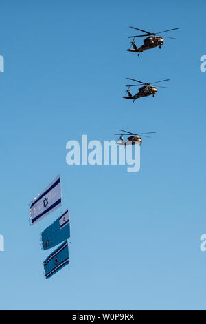Hazerim Air Base, Israel. 27th June, 2019. IAF Black Hawk helicopters drag flags at an air show taking place at a graduation ceremony honoring newly certified Israel Air Force pilots and navigators following their successful completion of one of the most competitive and rigorous training processes in the IDF at Hazerim Air Base in the Negev Desert. Credit: Nir Alon/Alamy Live News. - Stock Image