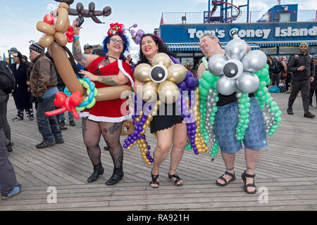 Three people in costumes with balloons on the Coney Island boardwalk prior to the annual Polar Bear Club New Year's day swim in Coney Island, NYC. - Stock Image
