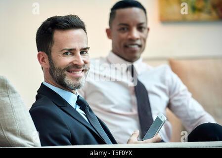 Businessmen sitting in hotel lobby - Stock Image
