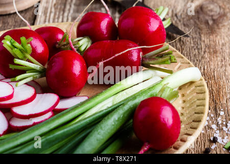Fresh springtime radishes, green onion and garlic on rustic wooden background, plant based food cooking  ingredients, close up, selective focus - Stock Image