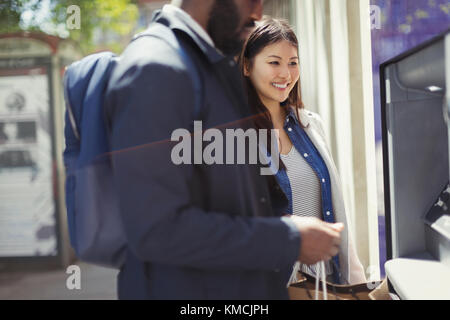 Young couple using ATM - Stock Image