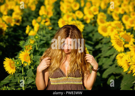 Lady in sunflower field - Stock Image