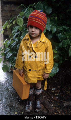 5 year old girl in a yellow raincoat and yellow lunch box wearing cowboy boots and orange hat - Stock Image