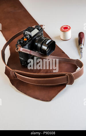 High angle close up of a vintage camera with handmade brown leather strap. - Stock Image