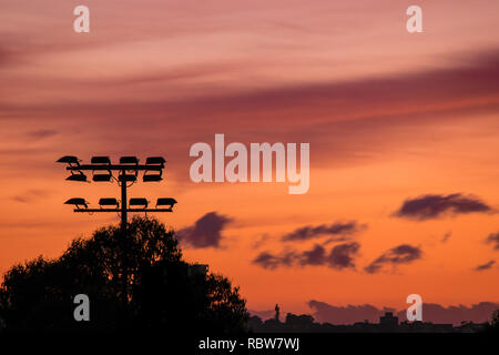 sports field light tower in silhouette at sunrise - Stock Image