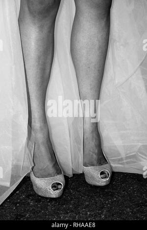 legs of a man disguised as a bridal woman - Stock Image