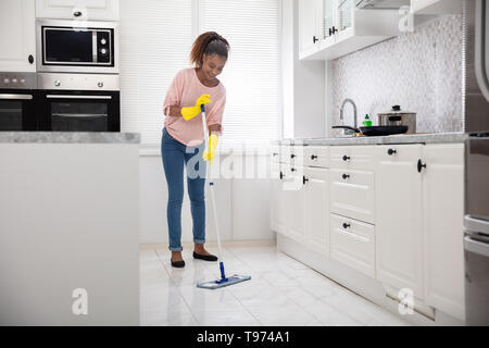 Smiling Female Janitor Cleaning White Floor With Mop In The Kitchen - Stock Image
