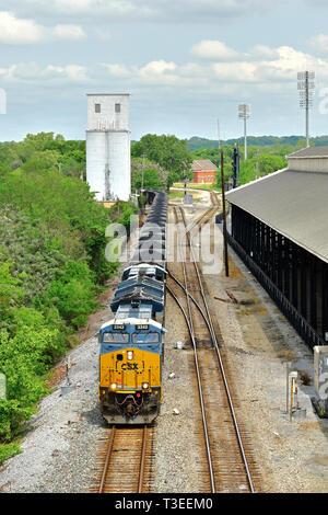 CSX Transportation GE ET44AH diesel locomotive pulls a long coal train in coal hopper cars through Montgomery Alabama, USA, switching yard. - Stock Image