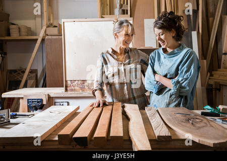 Two women choosing wood from a selection in a workshop - Stock Image