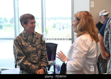 Col. Shannon Phares, 460th Medical Group commander, speaks to an attendee of the Retiree Appreciation Day event at Buckley Air Force Base, Colorado, Aug. 25, 2018. Over 30 various support agencies were available to provide an in-depth explanation on services they can provide. The hope is for retirees in the local community to feel welcomed and content with reaching out to Team Buckley for any information they may need. (U.S. Air Force photo by Senior Airman Jazmin Smith) - Stock Image
