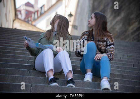 Two young women sitting on stairs holding a map and looking back. Mid shot - Stock Image