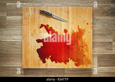 Blood and knife on the big wooden cutting board - Stock Image