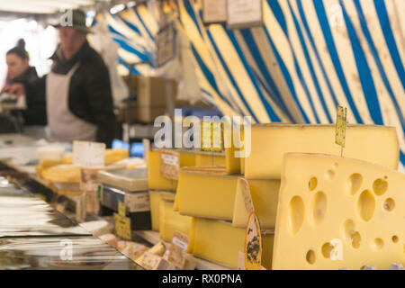 Semi-hard cheese sold at the Bastille market in Paris, France. - Stock Image