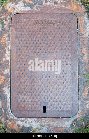 Old steel manhole cover plate over a water main valve in Spokane, Washington State, USA. - Stock Image