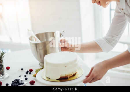 close up cropped photo. icing tips. chef working with an icing smoother - Stock Image